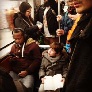 Photo of child reading on busy subway by Nathan Elliot.